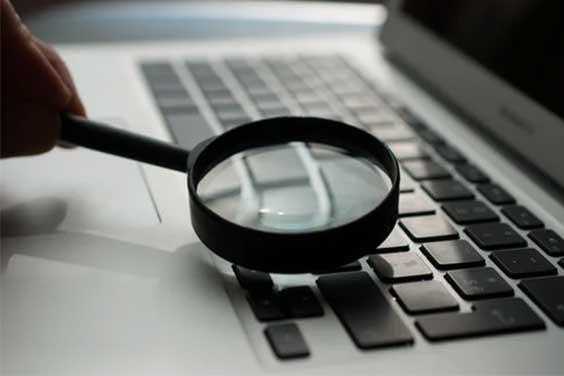 A-magnifying-glass-near-a-laptop-keyboard